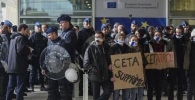 Policías belgas vigilan a los manifestantes concentrados frente al edificio de la Comisión Europea, durante la cumbre UE_canadá de octubre de 2016 en la que se firmó el CETA. AFP/jOHN tHYS