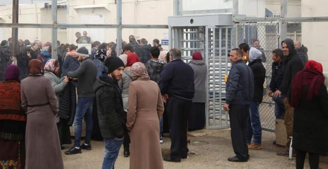 Familiares y amigos de la adolescente palestina Ahed Tamin, aguardan a las puertas del tribunal militar israelí, que la juzga por doce cargos por atacar a soldados, en la cárcel israelí de Ófer, cerca de la localidad cisjordana de Betunia. EFE/ Stringer