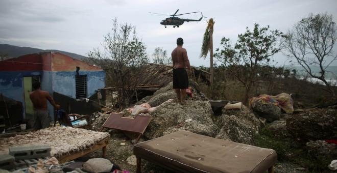 Un homme regarde un hélicoptère en Cajobabo (Cuba) après l'ouragan Matthew. / ALEXANDRE MENEGHINI (REUTERS)