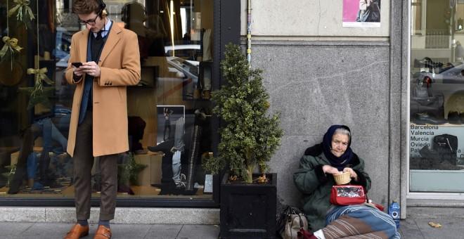 Un hombre consulta a su móvil junto a una tienda en cuya puerta hay una mujer pidiendo limosna, en el madrileño barrio de Salamanca. AFP/Gerard Julien