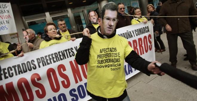 Dos afectados por las preferentes, con máscaras de Feijóo y Rajoy, durante una protesta. / EFE