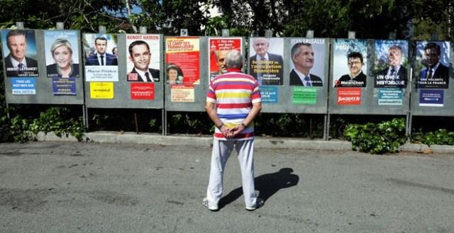 Un hombre mira los carteles de la campaña de los hasta 11 candidatos que se presentan a las elecciones presidenciales francesas. REUTERS/Eric Gaillard