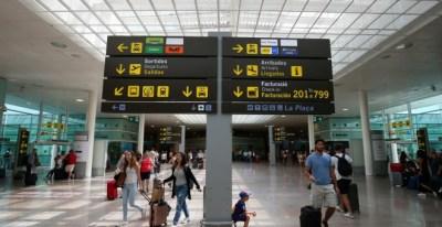 Viajeros junto a uno de los paneles informativos del Aeropuerto Barcelona-El Prat. REUTERS/Albert Gea