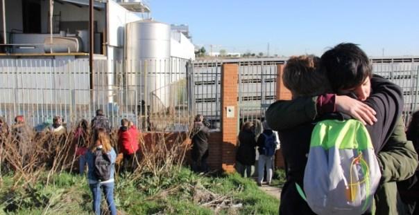 Dos de los asistentes a la vigilia se abrazan mientras presencian cómo se descarga un camión de cerdos./ Alejandro Tena