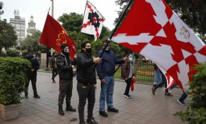 Miembros de la Sociedad Patriotas del Perú desfilan con banderas de la Cruz de Borgoña.