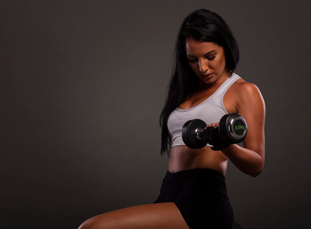 Young sexy fitness girl with weights on her hands