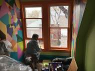 Betsy paints the green top and bottom of window.