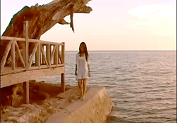 Photo of woman standing at edge of cement pier beside wooden deck