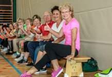 Ältere Menschen sitzen auf einer Bank in einer Sporthalle und heben ihre Daumen