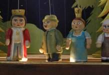 Ein Mann hält steht hinter einem Puppentheater und hält die Fäden von vier Puppen in der Hand.