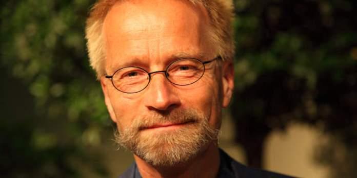 Mann mit Bart und Brille schaut in die Kamera.
