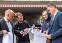 Vier Männer schauen sich Pläne an
