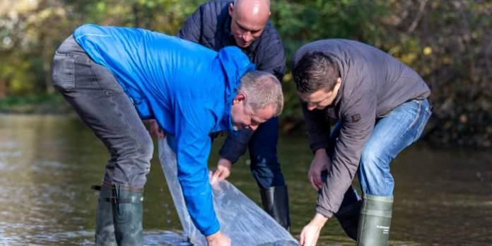 Drei Männer entlehren eine Plastiktüte ins fließende Wasser.