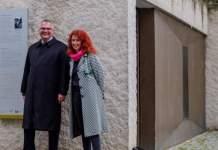 Zwei Personen stehen neben den Tafeln an der Mikwe in Erfurt.