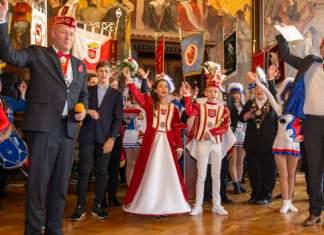 Zwei Herren mit Narrenkappe, ein Kinderprinzenpaar und mehrere Kinder im Tanzmariechenkostüm jubeln in einem Saal.