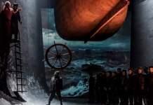 Opulentes düsteres Bühnenbild: Stahlwände, Schiffsrumpf von unten, Wasserbild und mehreren in Reihe stehenden Männern in Regenumhängen und mit Mützen