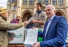 Vier Männer mit Papieren in den Händen stehen bei einem Traktor vor dem Rathaus.