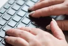 Tastatur eines PCs, darüber zwei Hände in der Grundhaltung zum Tastschreiben