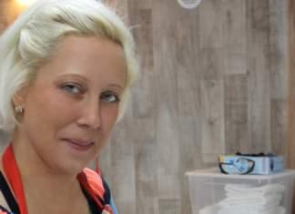 Eine Frau steht an einer Arbeitsplatte mit einer Waage, auf der ein Messbecher steht, den sie befüllen wird.