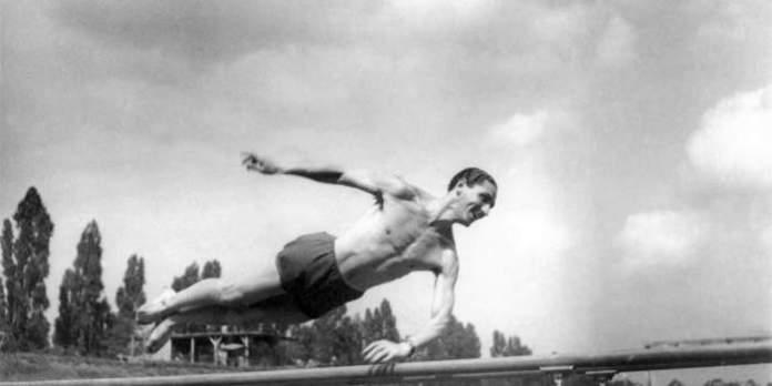 Ein Mann trainiert am Barren.