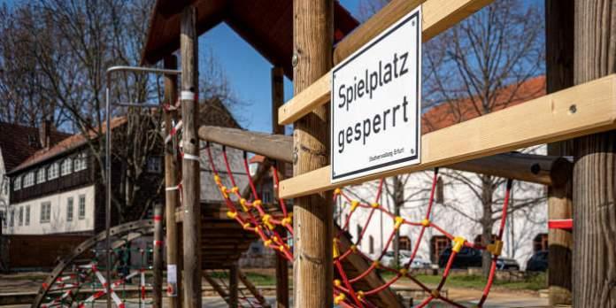 Ein Spielplatz mit einem Schild, auf dem zu lesen ist, dass der Spielplatz gesperrt ist.