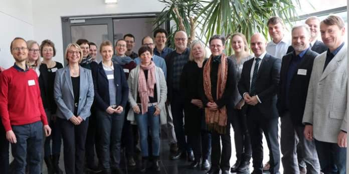 ein Gruppenfoto mit 23 Männern und Frauen