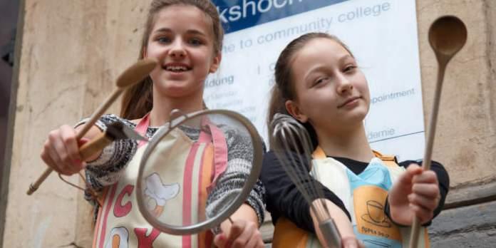 Zwei Mädchen mit Kochlöffel und Schöpfkellen vor dem Gebäude der Volkshochschule Erfurt.