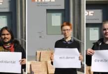 """Drei Menschen halten Blätter, auf denen die Worte """"Solidarität"""", """"mit denen"""" und """"die es brauchen"""" stehen."""