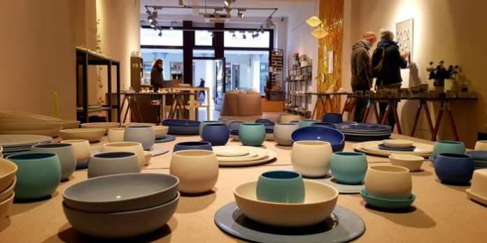 Teller, Schüsseln und Blumentöpfe in unterschiedlichen Farben aus Porzellan sind auf einem Tisch ausgestellt.