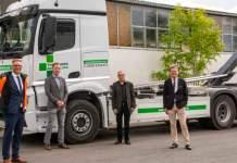 Vier Männer stehen vor einem LKW.
