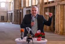 der Erfurter Oberbürgermeister präsentiert im Innenraum einer Kirche eine Buga-Dauerkarte im Chipkartenformat