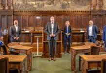 Fünf Personen stehen in einem mit dunklen Holz getäfelten Raum zwischen Stühlen und Bänken.