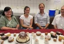Vier Personen sitzen an einem mit Kuchen gedeckten Tisch in einer Konditorei.