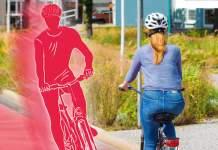 Auf einem Radweg fährt eine Frau Fahrrad, ihr kommt simuliert ein anderer Fahradfahrer entgegen.