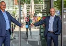 zwei Männer im Anzug stehen vor einer Schiebtür und zeigen auf einen Aufkleber