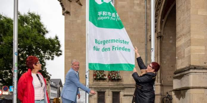 Eine Mann und eine Frau hissen eine Fahne. Auf dieser steht: Bürgermeister für den Frieden.