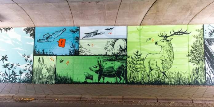 eine Wand in einem Tunnel ist mit verschiedenen Bildern im Comic-Stil bemalt