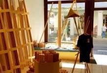 ein Raum mit Holzgestellen, Schaufenster und offener Tür zur Straße