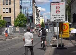Menschen überqueren zu Fuß und mit dem Rad die Gleise in einer Baustelle