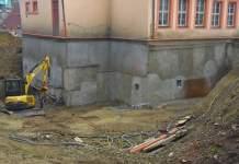 ein Bagger steht in einer Baugrube an einem Gebäude