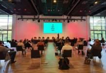 in einem Saal sitzen mehrere Tagungsteilnehmer, die eine Präsentation verfolgen