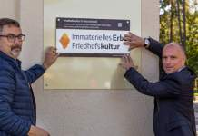 "zwei Männer halten eine Tafel mit der Beschriftung ""Immaterielles Erbe Friedhofskultur"""