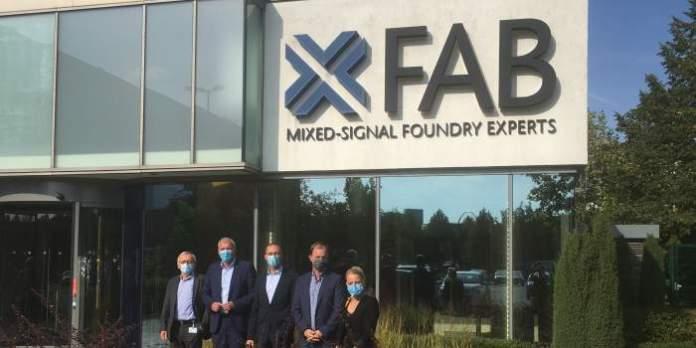 """Vier Männer und eine Frau stehen vor einem Firmengebäude mit dem Logo """"X-Fab""""."""