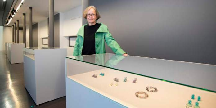 eine Frau steht an einer Ausstellungsvitrine mit Schmuckstücken