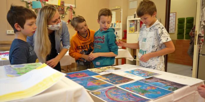 Vier Kinder und eine Erwachsene stehen um gemalte Bilder herum die auf einem Tisch liegen.