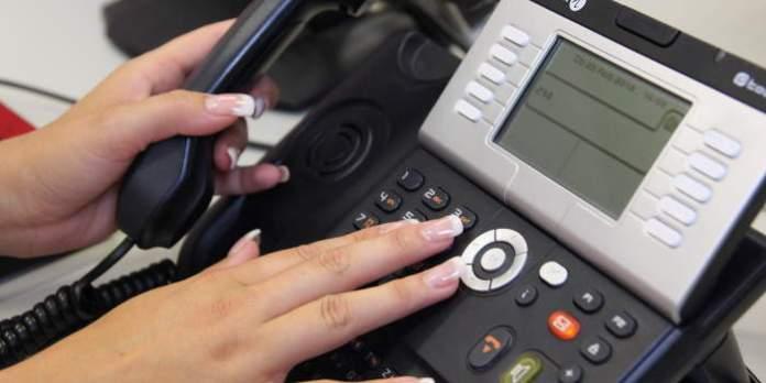 Detailaufnahme vom Bedienen eines Bürotelefons auf dem Schreibtisch