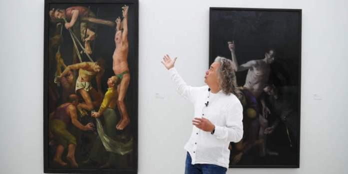 ein Mann erklärt ein Bild in einer Ausstellung