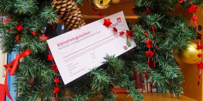 ein Bibliotheksgutschein in weihnachtlicher Dekoration mit Tannenkranz