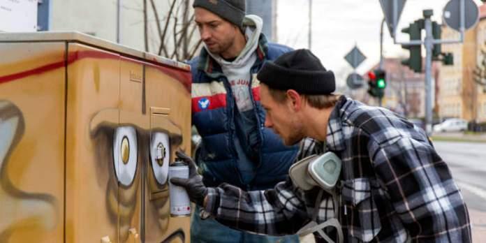 """Zwei junge Künstler sprühen """"Bernd das Brot"""" als Motiv auf einen Steuerungsschrank einer Ampel."""