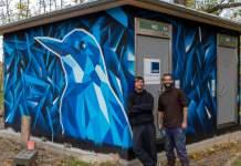 zwei Männer stehen vor einer Toilettenanlage, dessen Fassade ein Graffiti schmückt